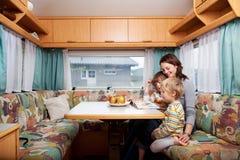 有读故事书的儿子的妇女在有蓬卡车的表上 免版税库存照片