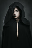 有黑斗篷的美丽的吸血鬼妇女 免版税库存图片