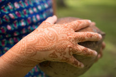 有临时无刺指甲花纹身花刺的女孩的手拿着一个椰子 库存照片
