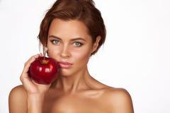 有黑暗的卷发、光秃的肩膀和脖子的年轻美丽的性感的女孩,拿着大红色苹果享受口味和节食, 免版税图库摄影