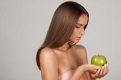 有黑暗的卷发、光秃的肩膀和脖子的年轻美丽的性感的女孩,拿着大绿色苹果享受口味和是dietin 免版税库存照片