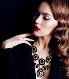有黑暗的卷发的妇女,佩带典雅的衣裳和珠宝项链 库存图片