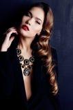 有黑暗的卷发的妇女,佩带典雅的衣裳和珠宝项链 免版税图库摄影