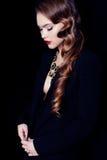 有黑暗的卷发的妇女,佩带典雅的衣裳和珠宝项链 图库摄影