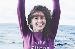 有黑暗的卷发的笑的女孩在刮风的天气的海滩 免版税库存图片