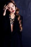 有黑暗的卷发的美丽的妇女,佩带典雅的衣裳和珠宝项链 免版税库存图片
