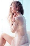 有黑暗的卷发的美丽的年轻新娘在摆在室的豪华婚礼礼服 库存图片