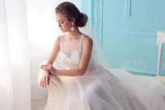 有黑暗的卷发的美丽的年轻新娘在摆在室的豪华婚礼礼服 库存照片