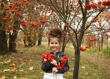 有黑暗的卷发的逗人喜爱的女孩在有花楸浆果花束的秋天森林里  免版税库存图片