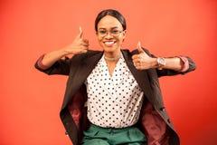 有黑暗的发光的皮肤的愉快的女实业家微笑和举行她的在红色背景的赞许 免版税库存图片