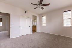有黑暗的地毯和吊扇的主卧室 免版税库存照片