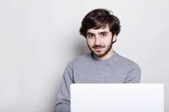 有黑暗的坐在开放便携式计算机前面的胡子和时髦的发型的一个确信的可爱的人有迷人的微笑lo 图库摄影