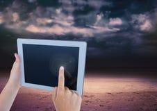 有黑暗的多云天空的手触板 库存照片