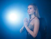 有黑暗的天使的妇女飞过祈祷在背景蓝色 免版税库存图片