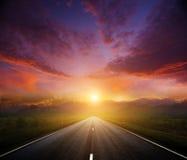 有黑暗的天空的乡下公路 免版税库存照片