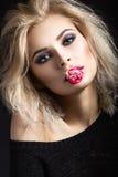 有黑暗的构成的美丽的白肤金发的女孩与在她的嘴唇的一朵花 秀丽表面 库存照片