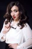 有黑暗的穿白色丝绸女衬衫的波浪发和红色嘴唇的美丽的年轻女商人保留玻璃的边在她的嘴 免版税库存图片