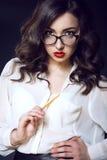 有黑暗的穿白色丝绸女衬衫的波浪发和红色嘴唇的美丽的年轻性感的女商人看起来直接在她的玻璃 库存图片