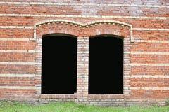 有黑暗的窗口孔的砖墙 库存图片