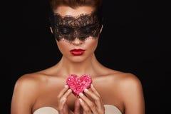 有黑暗的鞋带的年轻美丽的性感的妇女在眼睛露出肩膀和脖子,举行心脏蛋糕形状享受口味并且是 免版税库存图片