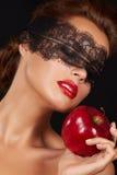 有黑暗的鞋带的年轻美丽的性感的妇女在眼睛露出肩膀和脖子,拿着大红色苹果享受口味并且是dietin 库存照片