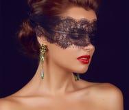 有黑暗的鞋带的年轻美丽的性感的妇女在眼睛露出肩膀和脖子,首饰耳环,感觉的诱惑,激情性红色l 库存图片