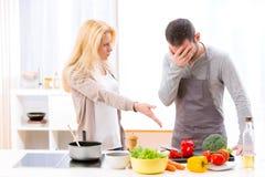 有年轻有吸引力的夫妇争论,当烹调时 免版税图库摄影