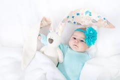 有绿松石花头饰带的可爱的逗人喜爱的新出生的女婴有复活节兔子的 库存照片