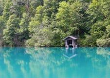 有绿松石水和船库的高山湖 免版税库存照片