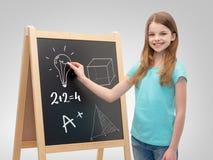 有黑板和白垩的愉快的小女孩 图库摄影