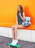 有滑板和背包的时尚俏丽的女孩 免版税库存照片