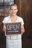 有黑板开放标志的俏丽的女服务员 图库摄影