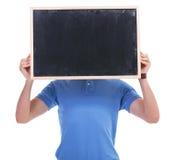 有黑板的偶然年轻人在面孔前面 免版税库存图片