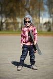 有滑板的小男孩在街道上 免版税图库摄影