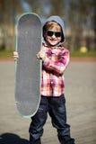 有滑板的小男孩在街道上 免版税库存图片