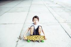 有滑板的小逗人喜爱的男孩在操场单独训练,做funy面孔 免版税图库摄影