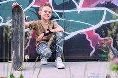 有滑板的男孩在街道画被绘的墙壁附近坐 库存图片