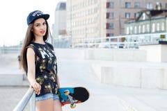 有滑板的美丽的女孩 免版税图库摄影