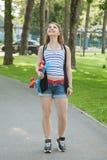 有滑板的逗人喜爱的女孩 免版税图库摄影