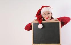 有黑板的滑稽的少妇在白色backgrou的圣诞老人帽子 免版税库存图片