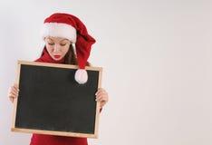 有黑板的滑稽的惊奇少妇在白色b的圣诞老人帽子 免版税库存图片