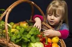 有水果和蔬菜篮子的女孩  免版税库存照片