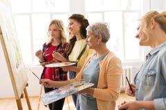 有画架和调色板的妇女在艺术学校 免版税库存图片