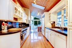 有黑桌面的白色厨柜在豪华房子里 免版税库存图片
