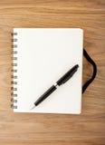 有黑橡皮筋和笔的被回收的纸笔记本 库存照片