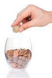 有2欧元硬币的与欧分的手和玻璃 库存图片