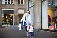 有年轻母亲和小孩的女孩乐趣购物 库存图片