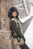 有黑毛皮盖帽和灰色背心的可爱的妇女享受冬天的 侧视图时兴深色女孩摆在 免版税库存照片
