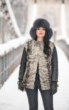 有黑毛皮盖帽和灰色背心的可爱的妇女享受冬天的 前面看法时兴深色女孩摆在 免版税库存照片