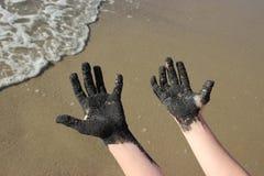 有黑沙子的手在海滩 免版税图库摄影